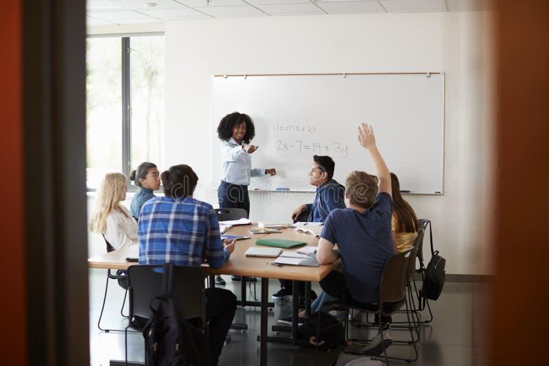 Whiteboard教的算术类的女性高中家庭教师与问的学生问题 免版税库存照片