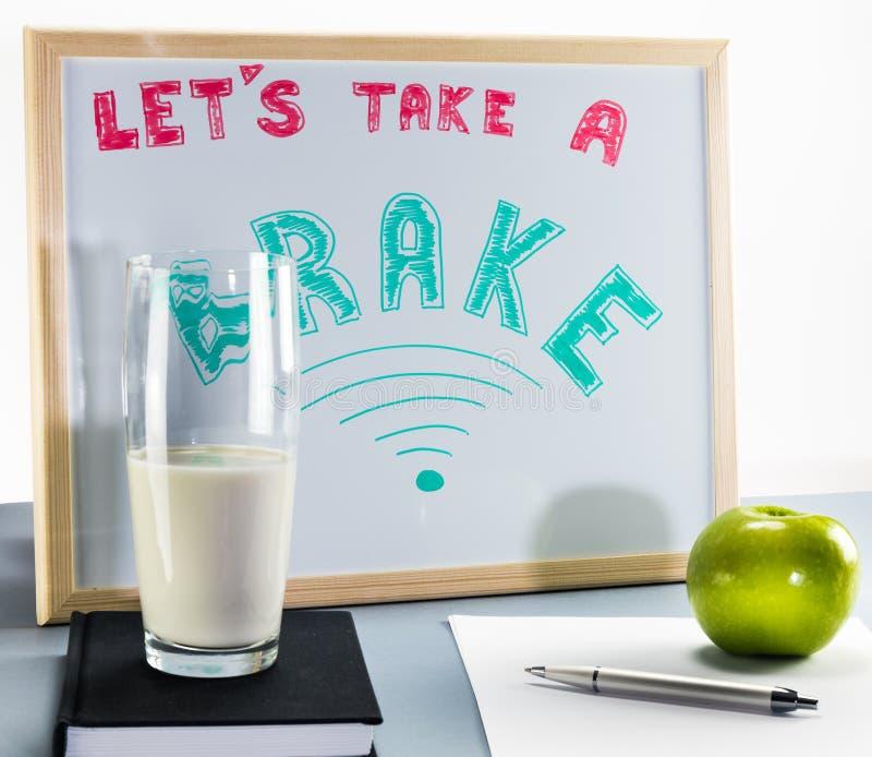 Whiteboard озаглавило ` позволило ` s принять ` тормоза с красными и зелеными письмами, чашку молока и зеленое яблоко стоковое изображение