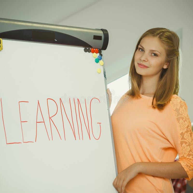Девушка студента писать учащ слово на whiteboard стоковые изображения