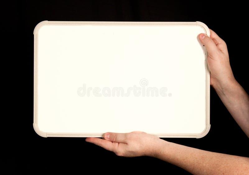 Whiteboard en las manos del hombre en negro imagen de archivo libre de regalías