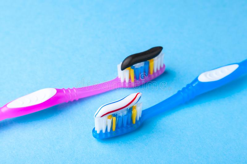 Whitening toothpaste is usual colored and black from charcoal on toothbrush. Concept. Which toothpaste to choose?. How to whiten your teeth stock image