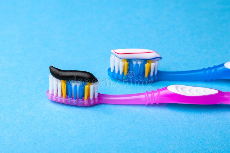 Whitening toothpaste is usual colored and black from charcoal on toothbrush. Concept. Which toothpaste to choose?. How to whiten your teeth royalty free stock photo