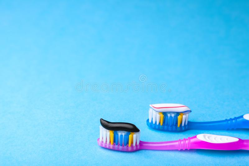 Whitening toothpaste is usual colored and black from charcoal on toothbrush. Concept. Which toothpaste to choose?. How to whiten your teeth? Copy space for text royalty free stock images