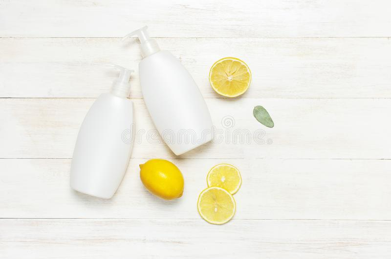 Whites Cosmetic bottle containers and fresh lemon on white wooden background top view flat lay copy space. Blank label for stock photography