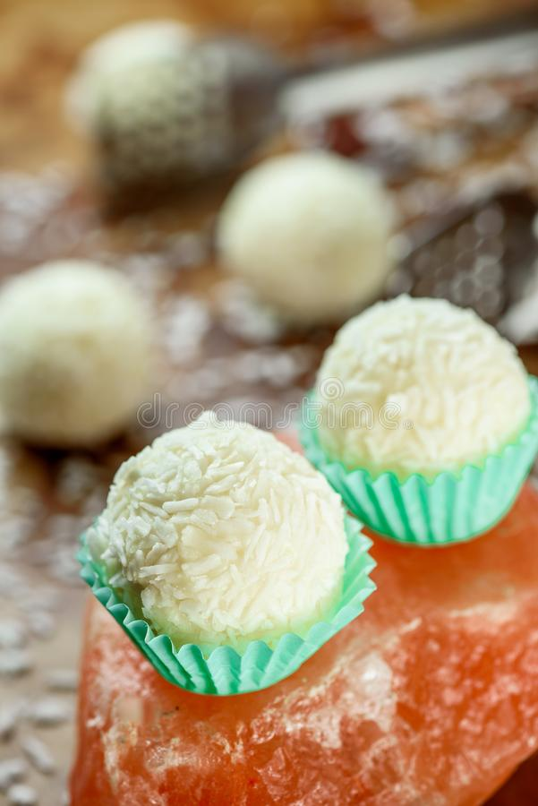 Whites Vegan raw candies with coconut flakes without sugar and milk on a beautiful brass background. raw food dessert. Close-up stock image