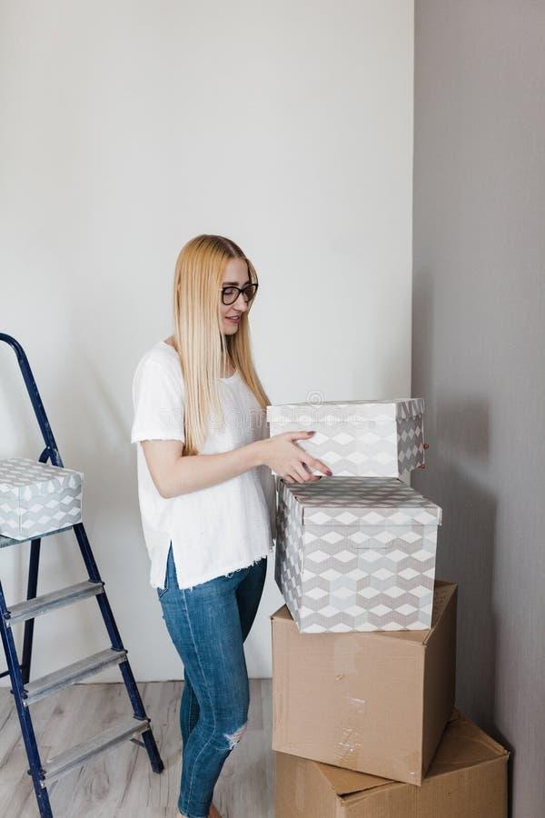 whitet衬衣身分的年轻白肤金发的愉快的妇女在有一些移动的箱子的空的墙壁上 免版税库存图片
