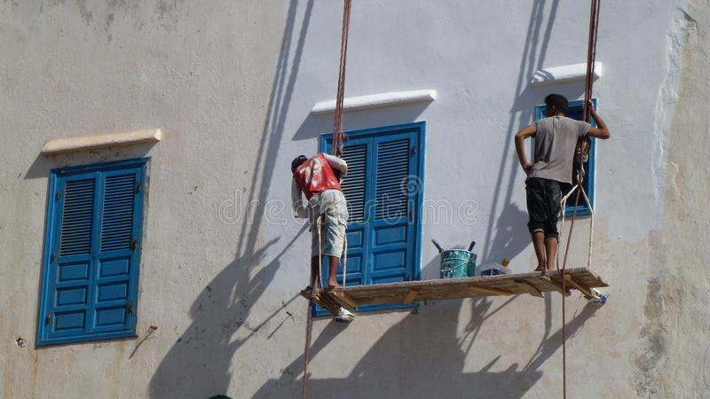 Whitewash painting - Africa. House painting, whitewash walls, tradesmen, makeshift scaffolding royalty free stock photo