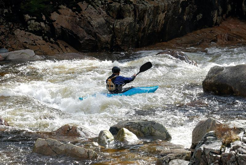 Whitewater canoeing on rough water in rugged rocky river stock photography