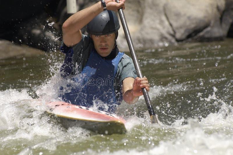 Whitewater del hombre joven kayaking fotos de archivo libres de regalías