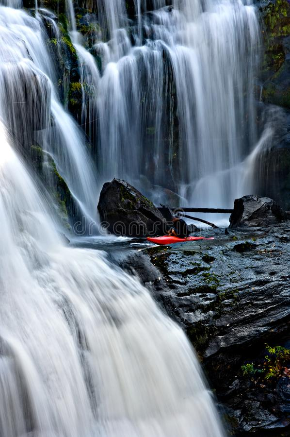 Whitewater kayaker preparing to paddle over a waterfall. Whitewater kayaker preparing to paddle over mountain waterfall dropping over smooth moss rocks in stock photos