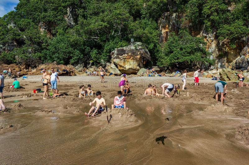WHITIANGA, NZL - March 07 2016:Visitors making small hot water pools in Hot Water beach stock images