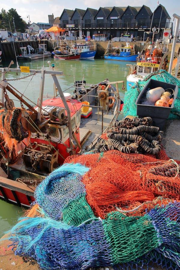 WHITSTABLE, REGNO UNITO - 15 OTTOBRE 2017: Il porto di pesca con le reti da pesca variopinte nella priorità alta e le capanne di  immagine stock libera da diritti