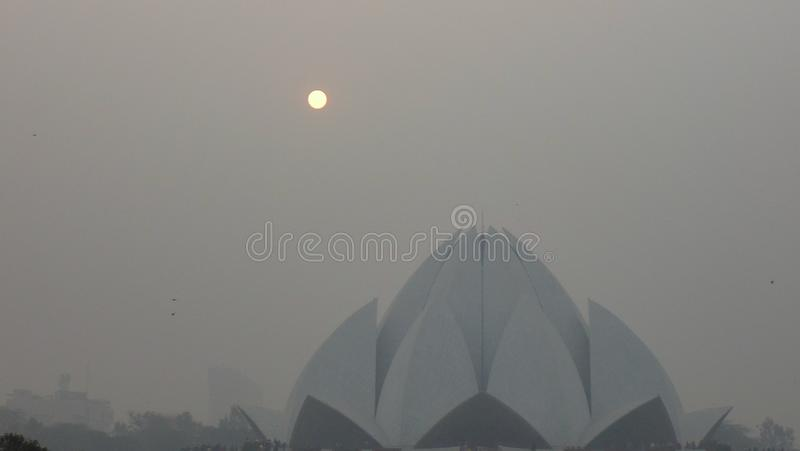 White Lotus temple in Delhi, India. Whitw Lotus temple on a foggy day and sun set in Delhi, India stock images