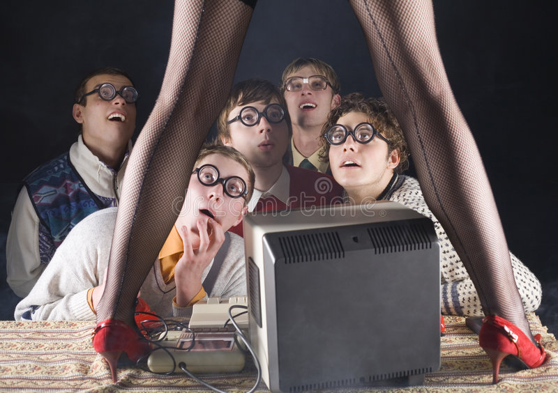 Who is she...?. Five nerdy guys sitting in front of old-fashioned computer and stripteaser. They are looking fascinated. Front view stock photography