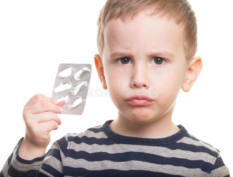 Who ate that?. Sad kid with empty blister on isolated white stock images