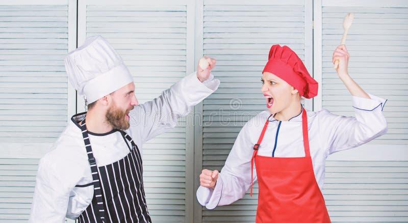 Who betere kok Culinair slagconcept De culinaire vrouw en de gebaarde man tonen concurrenten Uiteindelijke het koken uitdaging royalty-vrije stock afbeelding