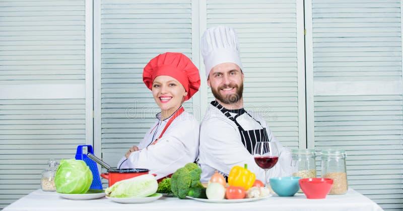 Who betere kok gelukkig paar in liefde met gezond voedsel man en vrouwenchef-kok in restaurant vegetari?r kokpaar binnen royalty-vrije stock foto's