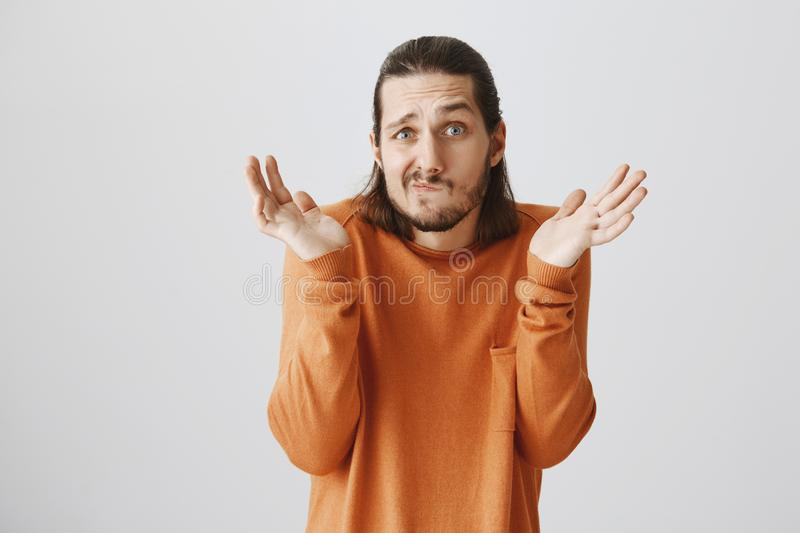 Who cares, I am indifferent. Funny confused adult bearded guy in orange sweater shrugging with spread hands near. Shoulders, making puzzled face, being unaware stock photos