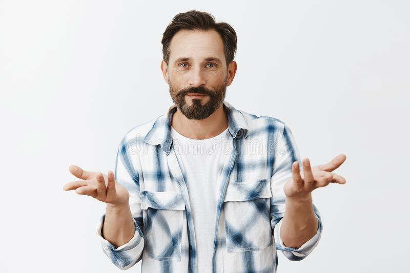 Who cares, realxed and chill. Portrait of calm and indifferent attractive male model with beard, raising palms in stock photo