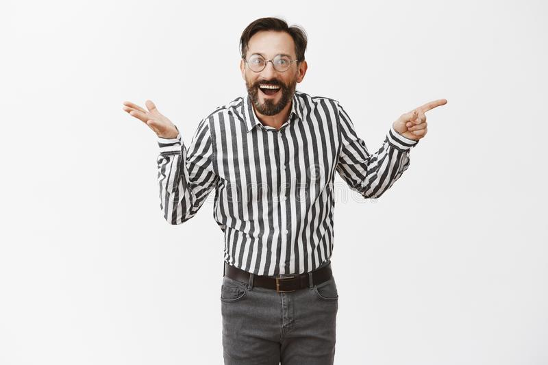Who could thought. Impressed happy and surprised attractive mature male with beard in glasses and formal shirt, pointing royalty free stock image