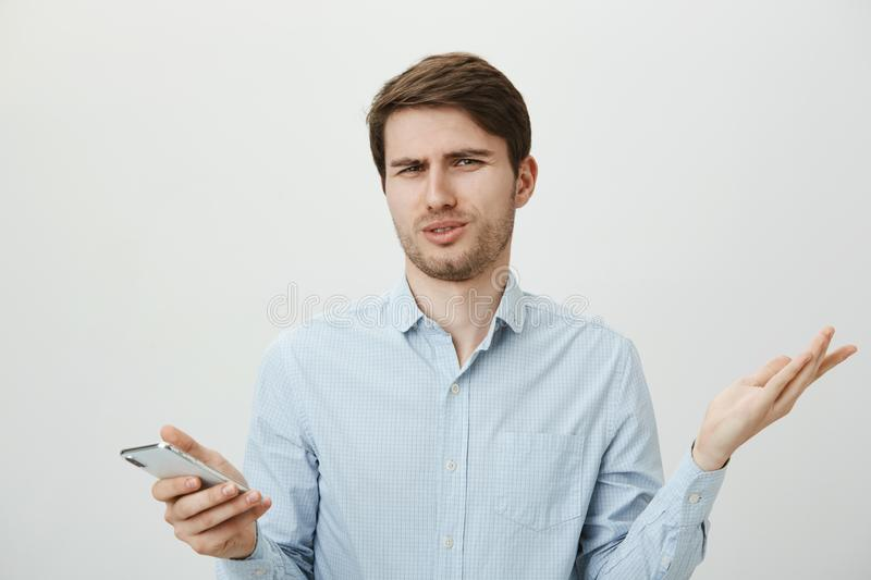 Who on Earth can write such stupid message. Portrait of confused and bothered handsome european employee shrugging with. Questioned and annoyed expression stock images
