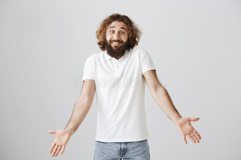 Who knew about consequences. Portrait of clueless carefree eastern male with beard and curly hair, smiling awkwardly and. Shrugging with spread palms, being royalty free stock images