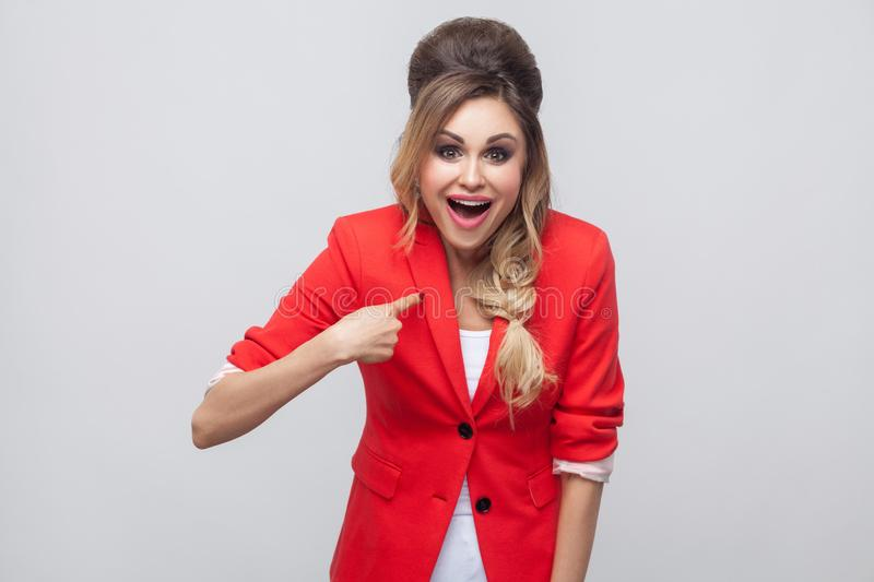 Who? me? Excited beautiful business lady with hairstyle and makeup in red fancy blazer, standing, pointing herself and looking at. Camera with amazed face stock photography
