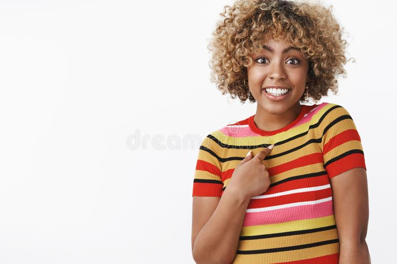 Who me. Portrait of surprised cute and carefree charming african-american girl pointing questioned and excited at. Herself as being mentioned or picked smiling royalty free stock photo