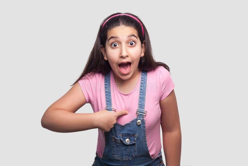 Who? me? Portret van geschokt donkerbruin meisje in toevallige roze t-shirt en blauwe overall status die, richtend, camera bekijk stock foto