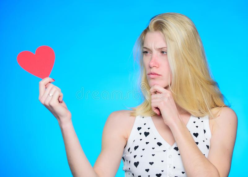 Who is my valentine. Love and romance. thoughtful woman on blue background. woman with decorative heart. Date royalty free stock image
