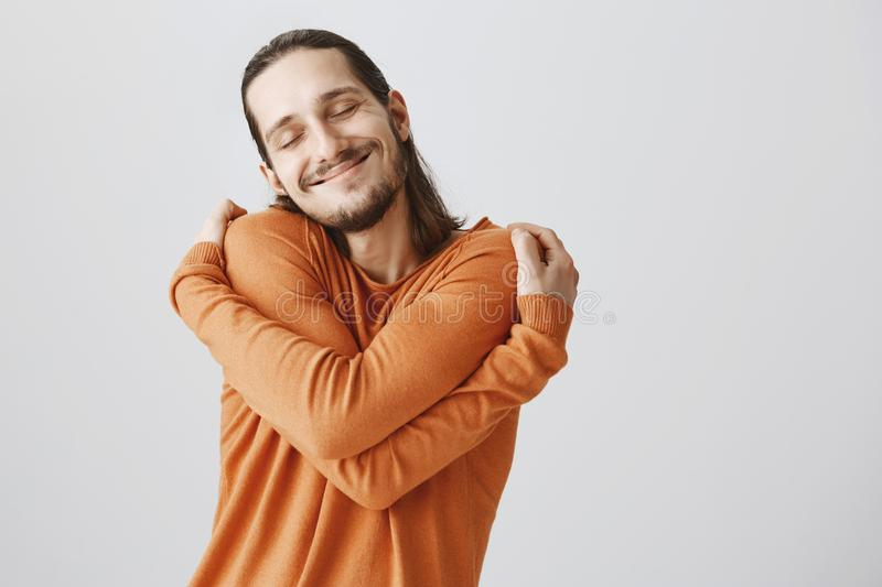 Who need girlfriends if you can hug yourself. Funny playful european guy with long hair and beard cuddling himself and stock images