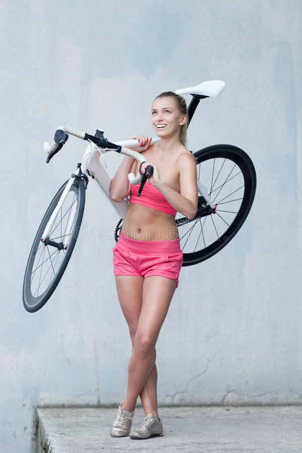 Who is riding who?. Girl holding bicycle and foretasting the ride royalty free stock photo