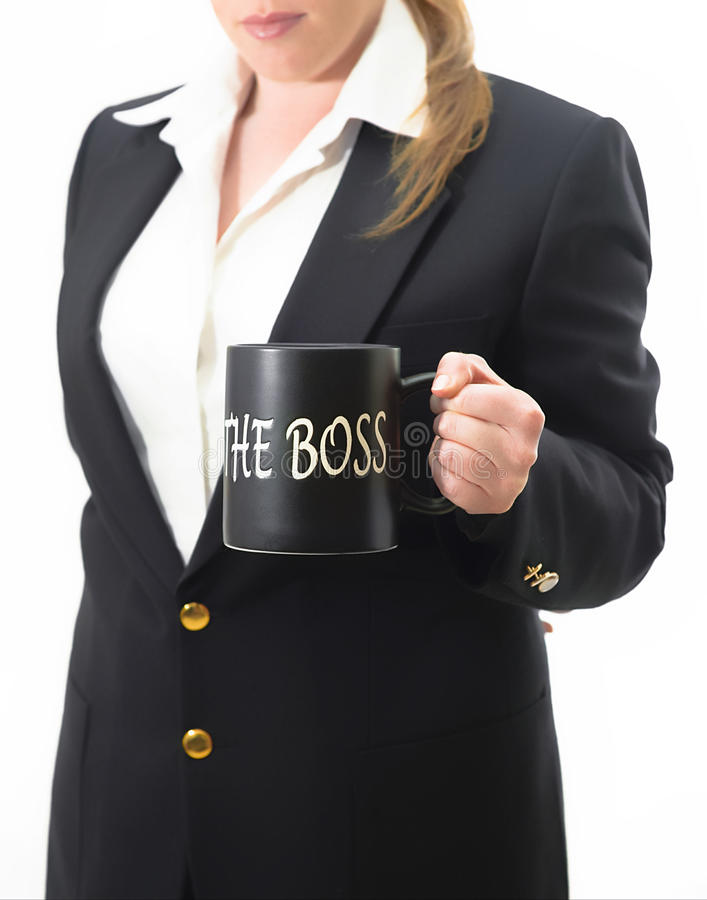 Who's the boss?. A woman demonstrating her power by holding a mug with written words 'THE BOSS royalty free stock photography