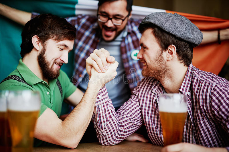 Who is stronger. Two strong young men arm-wrestling in pub stock photography