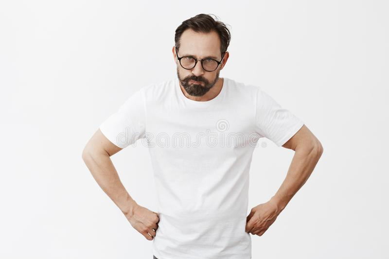 Who took my phone. Angry displeased good-looking adult father in white t-shirt and sunglasses, holding hands on waist stock photo