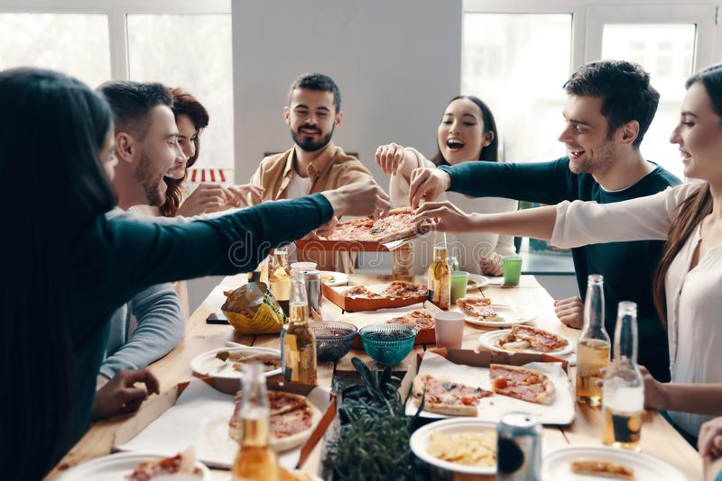 Who wants more pizza?. Group of young people in casual wear picking pizza and smiling while having a dinner party indoors royalty free stock image