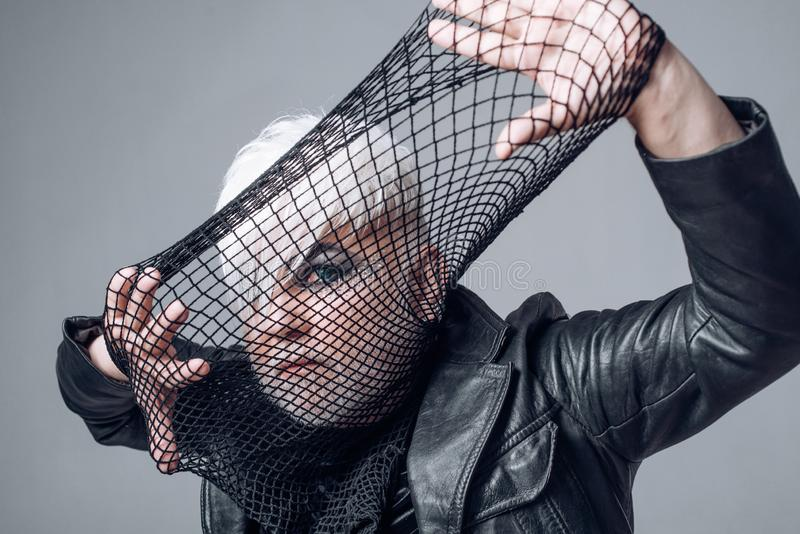 Who wants to play. Transgender man cover face with fishnet. Male makeup look. Fetish fashion. BDSM fashion accessory. Heterosexual man with male makeup stock image