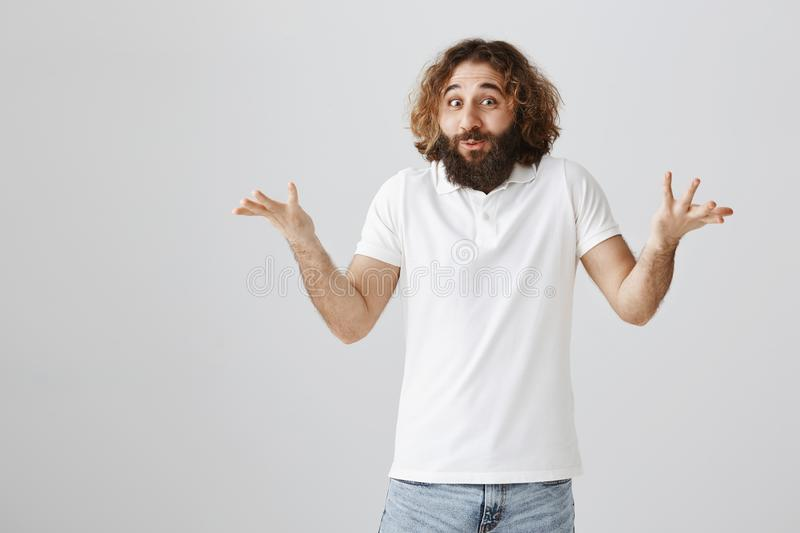 Who would expect this will happen. Portrait of funny emotive adult guy with long beard and messy curly hair shrugging. With raised palms and smiling with folded royalty free stock photos