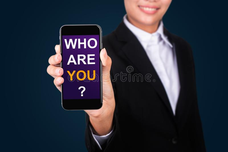 Who Are You?, Happy businesswoman Show text Who Are You? on smart phone royalty free stock photos
