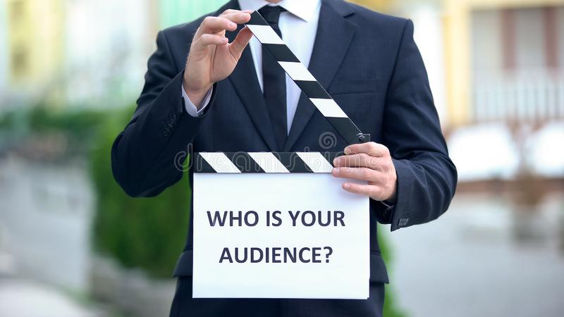 Who is your audience question on clapperboard in hands of male celebrity, pr stock image