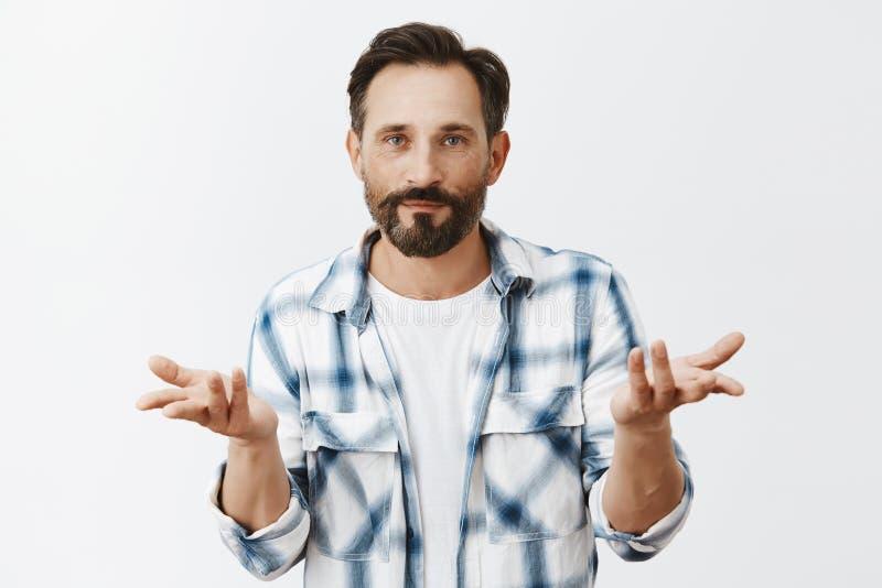 Who zorgen, realxed en kou Portret die van kalm en onverschillig aantrekkelijk mannelijk model met baard, palmen binnen opheffen stock foto