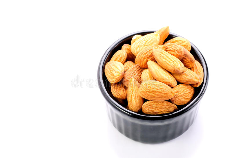 Whole almond nuts. In ramekin on white background stock photography