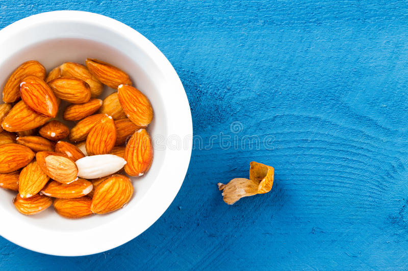 Whole almonds soaked in water over blue table royalty free stock photography
