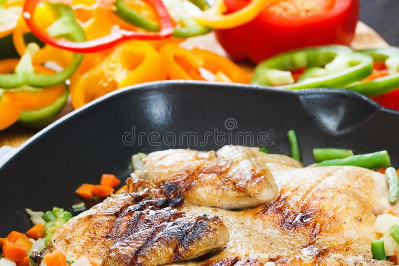 Whole appetizing grilled chicken on grill pan with vegetables royalty free stock photography
