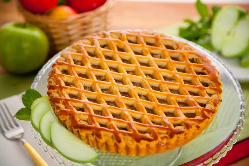 Whole apple pie tart served on a table basket of fruit green golden dessert. Vertical slice of apple pie tart cake dessert sweet treat Entire whole apple pie stock photo