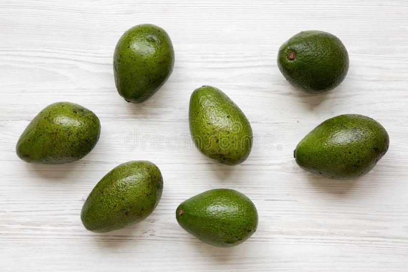 Whole avocados on white wooden background, top view. Flat lay, overhead stock image