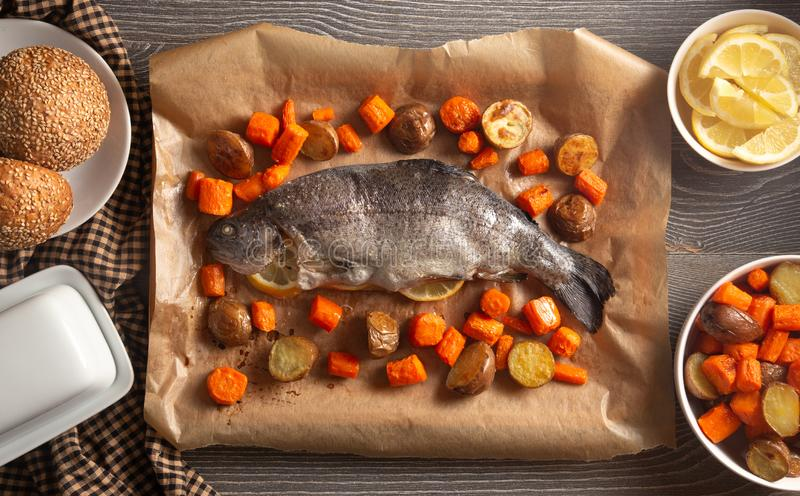 Whole Baked Rainbow Trout on a Table Set for Dinner. A Whole Baked Rainbow Trout on a Table Set for Dinner royalty free stock photography