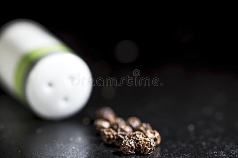 Whole black peppercorns and white salt shaker on a black background, isolated stock photos