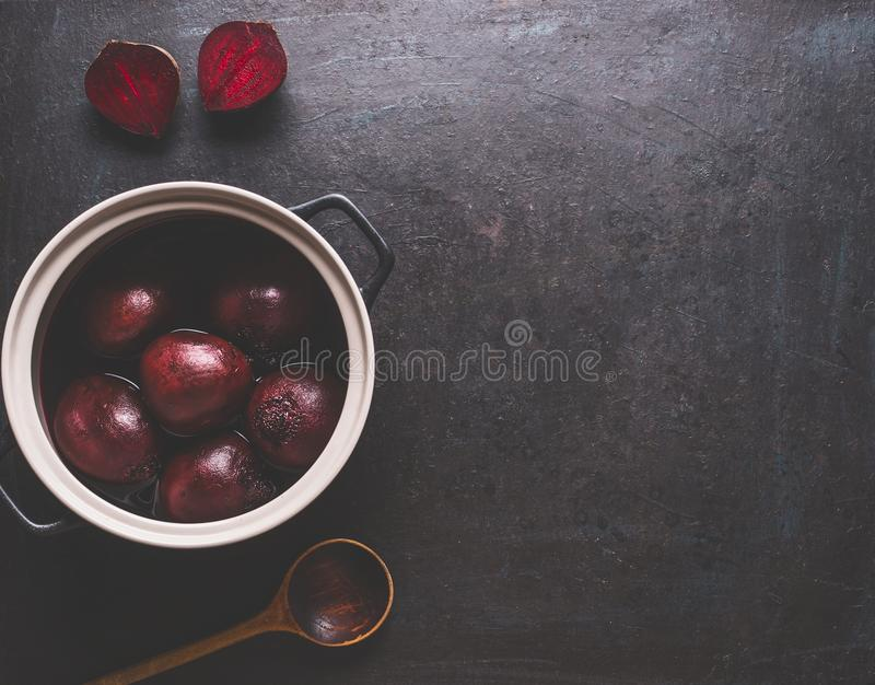 Whole boiled beet roots in cooking pot with wooden spoon on dark background, top view with copy space for your design and recipes. Healthy clean, low calories stock photo