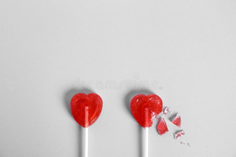 Whole and broken heart shaped lollipops on white background, top view. Space for text royalty free stock image